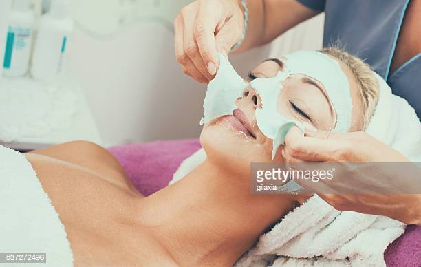 peeling of facial mask. - beauty care occupation stock photos and pictures