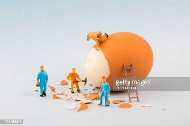 peeling off the hard egg shell. figurines work hard - 皮をむく ストックフォトと画像