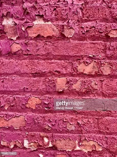 Peeling paint on brick wall