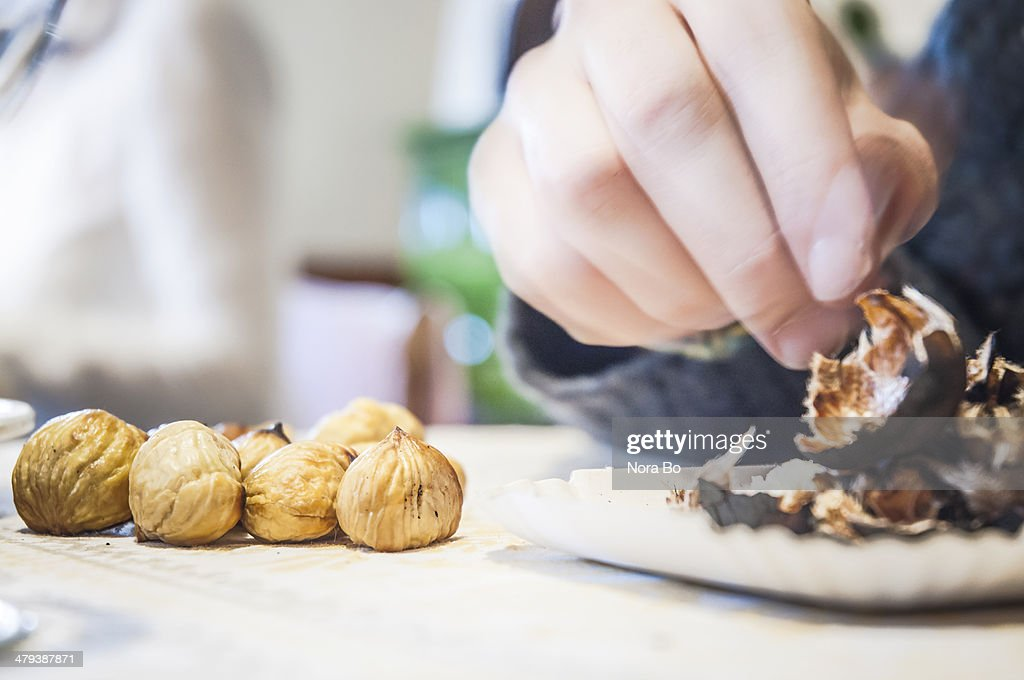 Peeling roasted chestnut- Keschtn during Törggelen : Stock Photo