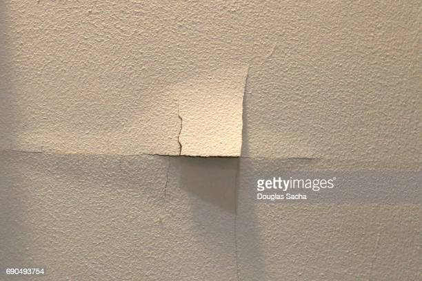 Peeling wallpaper on a white colored wall