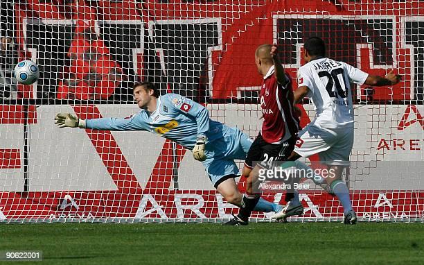 Peer Kluge of Nuernberg scores a goal against goalkeeper Christopher Heimeroth of M'gladbach during the Bundesliga match between 1. FC Nuernberg and...