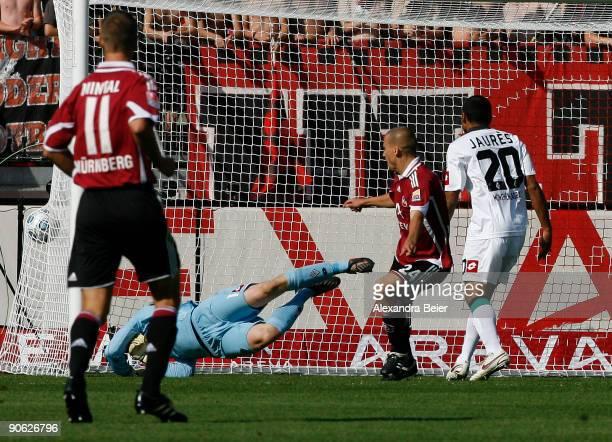 Peer Kluge of Nuernberg scores a goal against goalkeeper Christopher Heimeroth of M'gladbach as his teammate Jean-Sébastien Jaurès and Marek Mintal...