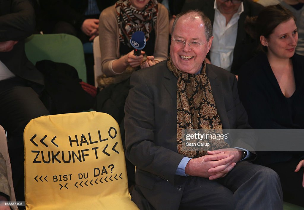 "Peer Steinbrueck, candidate for chancellor of the German Social Democrats (SPD), sits next to an empty seat with the inscription 'Hello Future, Are you there?' while attending a rehearsal of ""Junges Deutsches Theater"" (Young German Theater) at the Deutsches Theater during a tour of enterprises in Berlin on April 3, 2013 in Berlin, Germany. Steinbrueck will challenge German Chancellor Angela Merkel in federal elections scheduled for September, though so far he is trailing significantly in polls."