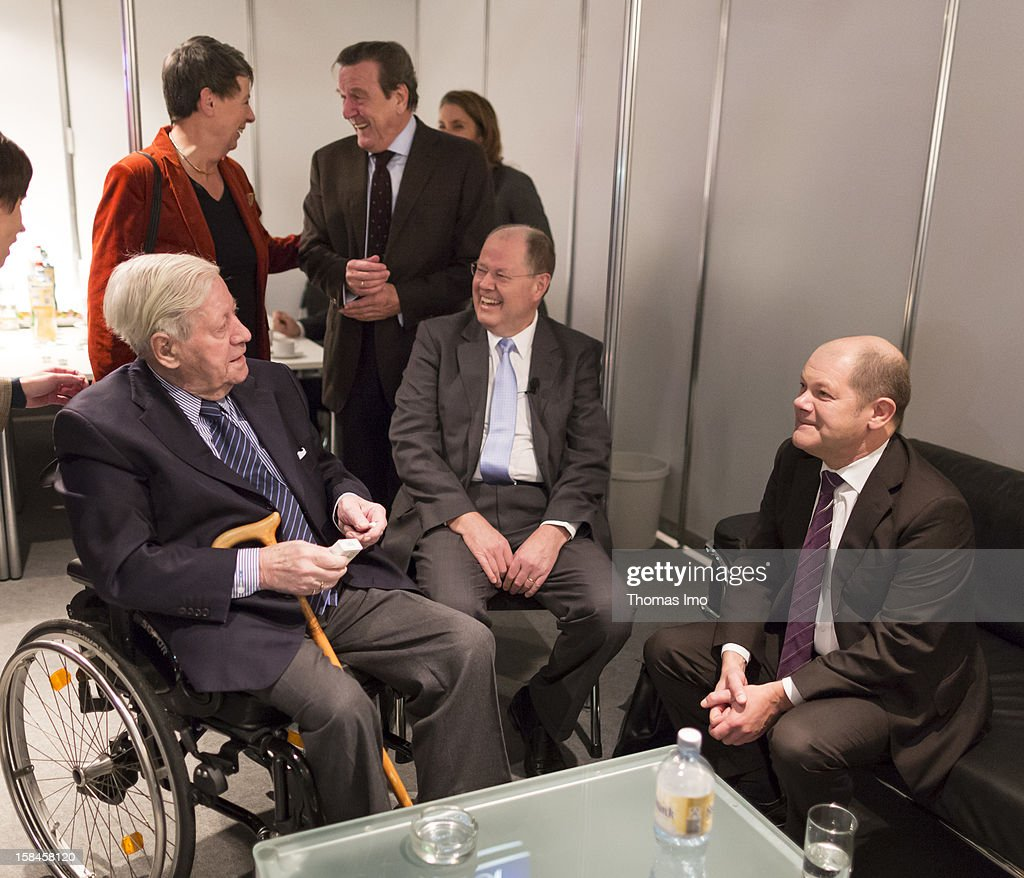 Peer Steinbrueck (C), chancellor candidate of the German Social Democrats (SPD) talks with former federal chancellor Helmut Schmidt (L) and Hamburg Mayor Olaf Scholz (R) before beginning of the SPD federal party convention on December 9, 2012 in Hanover, Germany. The SPD is convening to set its policy course for the next year and to celebrate Steinbrueck, who will run for chancellor in elections set for 2013.