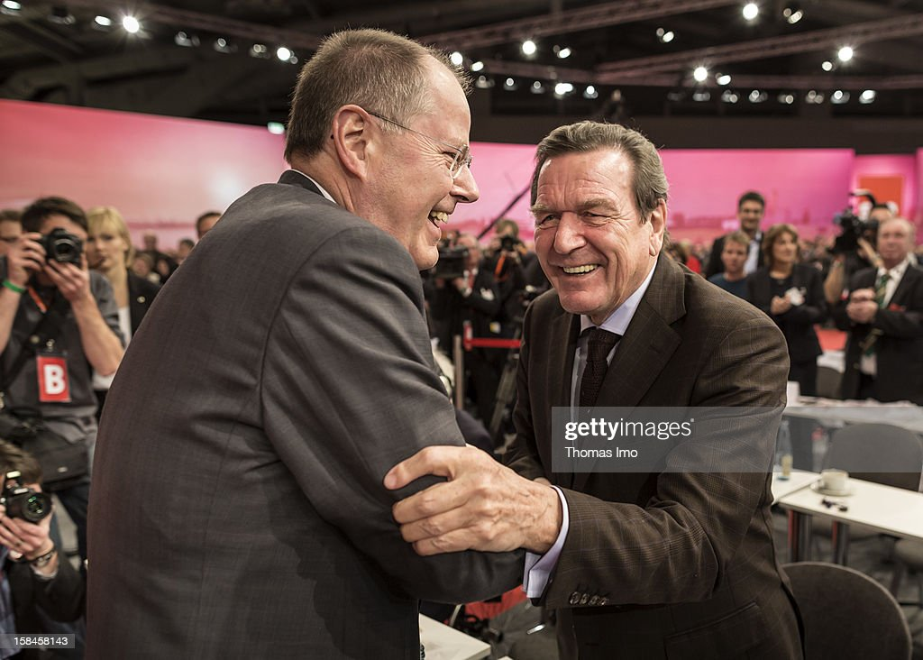 Peer Steinbrueck (L), chancellor candidate of the German Social Democrats (SPD) shakes hands with former federal chancellor Gerhard Schroeder after his speech at the SPD federal party convention on December 9, 2012 in Hanover, Germany. The SPD is convening to set its policy course for the next year and to celebrate Steinbrueck, who will run for chancellor in elections set for 2013.