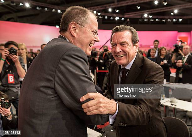 Peer Steinbrueck chancellor candidate of the German Social Democrats shakes hands with former federal chancellor Gerhard Schroeder after his speech...