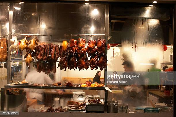 Peering through the steamy window of a Chinese restaurant in London's Chinatown district we see the shapes and forms of kitchen staff and customers...