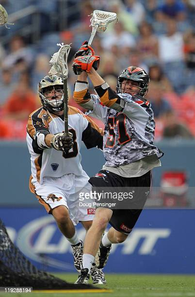 Peet Poillon of the Denver Outlaws controls the ball as Dan Groot of the Rochester Rattlers defends during their Major League Lacrosse game at...