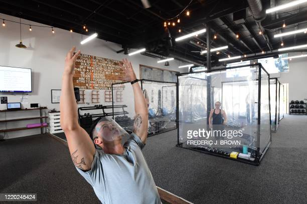 Peet Sapsin leads a class at Inspire South Bay Fitness with students behind plastic sheets in their workout pods while observing social distancing on...