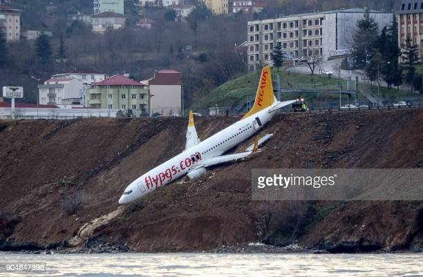 A Pegasus Airlines Boeing 737 passenger plane is seen struck in mud on an embankment a day after skidding off the airstrip after landing at Trabzon's...