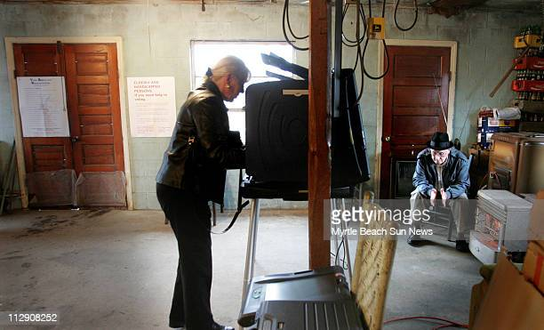 Peggie Shannon fills out her paper ballot in a nonfunctioning electronic polling station while Albert Lewis warms his hands by a heater at the...
