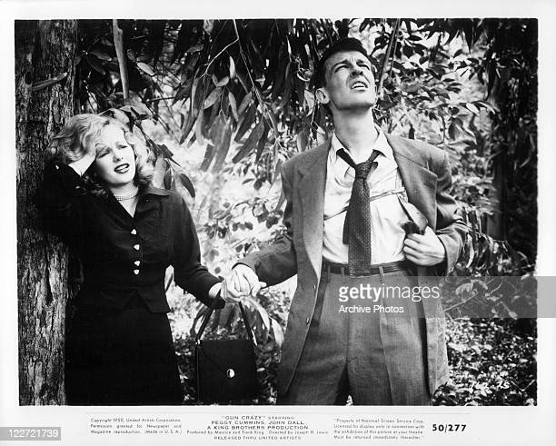 Peggy Cummins holds hand with John Dall in a scene from the film 'Gun Crazy' 1950