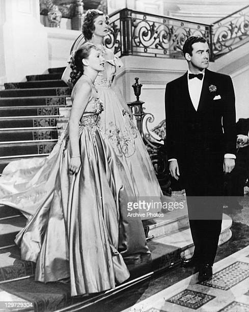 Peggy Cummins Myrna Loy and Richard Greene standing at stairwell looking in the same direction in a scene from the film 'If This Be Sin' 1949