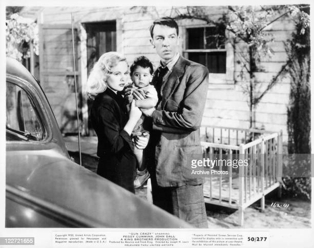 Peggy Cummins stands holding baby with male actor in a scene from the film 'Gun Crazy' 1950