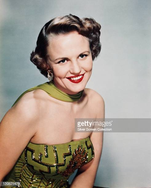 Peggy Lee US singer songwriter and actress smiling wearing a green strapless dress and a green scarf in a studio portrait against a pale blue...