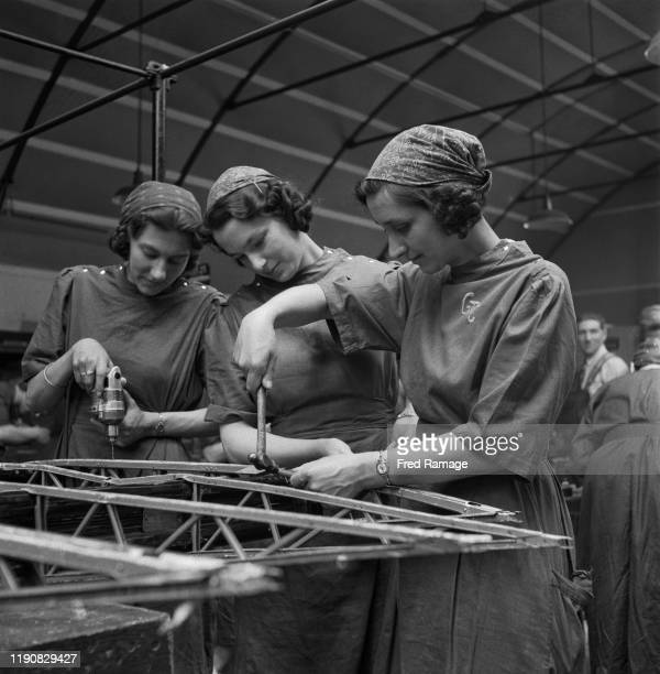 Peggy Rowland Betty Pridie and Rose Pridie members of the GTC at work putting rivets in the wing of an aircraft at the Slough Training Centre in...