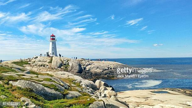 peggys point lighthouse on rock formation by sea against sky - nova scotia stock pictures, royalty-free photos & images