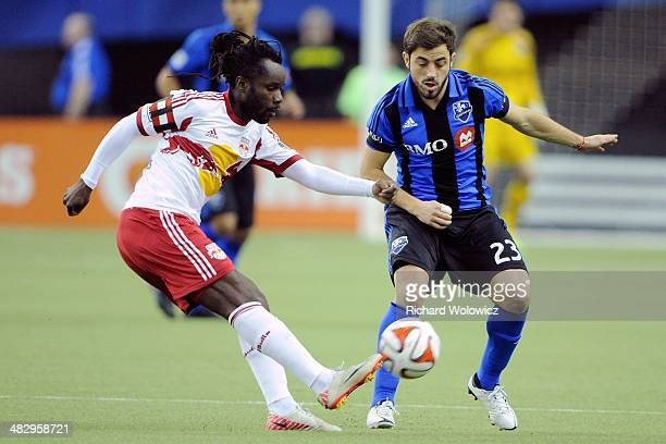 Peguy Luyindula of the New York RedBulls kicks the ball in front of Hernan Bernardello of the Montreal Impact during the MLS game at the Olympic...