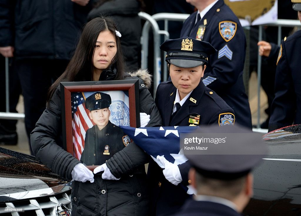 Pei Xia Chen (L), widow of New York Police Officer Wenjian Liu , walks with his portrait during the funeral for Officer Wenjian Liu in the Dyker Heights neighborhood on January 4, 2015 in the Brooklyn borough of New York City. Liu was killed with his partner Rafael Ramos on December 20 when the two were shot by Ismaaiyl Brinsley while sitting in their patrol car.