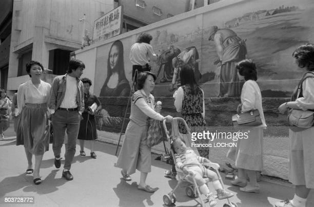 Peintre dans les rues de Tokyo réalisant sur un mur 'La Joconde' et 'Les Glaneuses' en mai 1979 au Japon