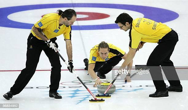 Peja Lindholm of Sweden slides the stone as teammates Peter Narup and Magnus Swartling sweep during the preliminary round of the men's curling...