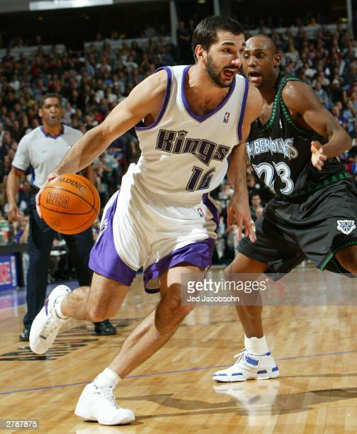 Peja Stojakovic of Sacramento Kings drives by Trenton Hassell of the Minnesota Timberwolves during an NBA game on December 5 2003 at Arco Arena in...