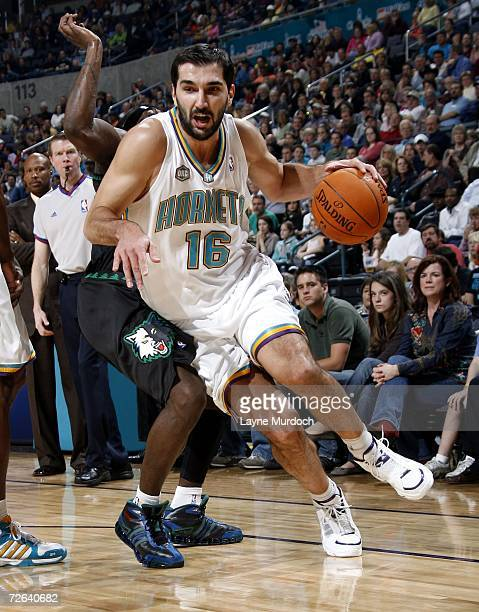 Peja Stojakovic of the New Orleans/Oklahoma City Hornets dribbles around Ricky Davis of the Minnesota Timberwolves during an NBA game on November 24...