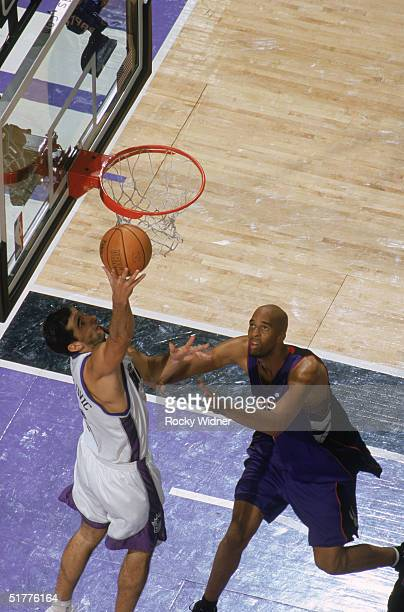 Peja Stojakovic of the Sacramento Kings shoots from under the basket against Loren Woods of the Toronto Raptors during the game at Arco Arena on...