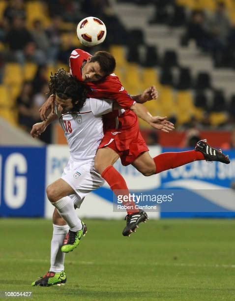 Pejman Nouri of Iran is challenged by An Yong Hak of DPR Korea during the AFC Asian Cup Group D match between DPR Korea and Iran at Qatar Sports Club...