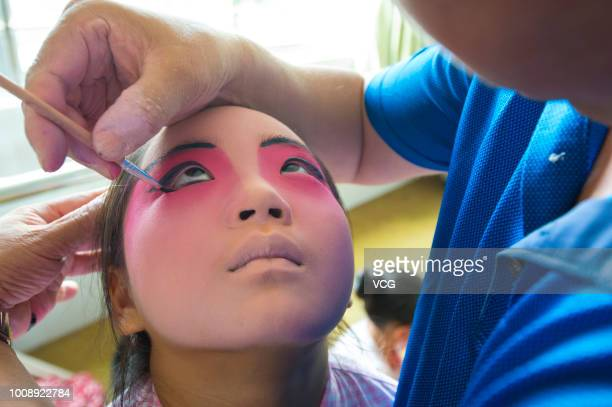 Peking Opera teacher applies makeup for a primary school student during summer holiday on July 28 2018 in Haian Jiangsu Province of China To promote...