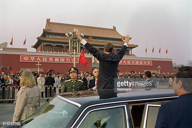 President George Bush waves to a crowd of Chinese onlookers in Tiananmen Square on Saturday after his motorcade stopped in route to the guest house...