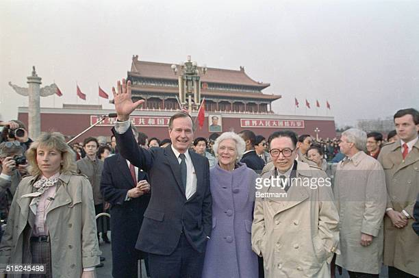 US President George Bush and his wife Barbara wave to crowds of Chinese onlookers after their motorcade made a stop at Tiananmen Square on Saturday