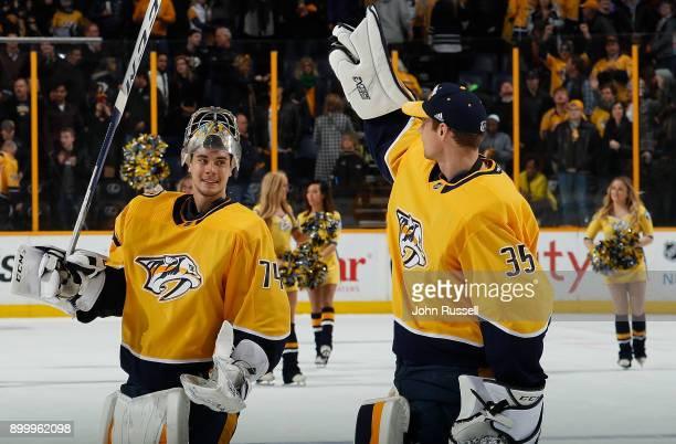 Pekka Rinne congratulates Juuse Saros of the Nashville Predators on his 30 shutout win against the Minnesota Wild during an NHL game at Bridgestone...