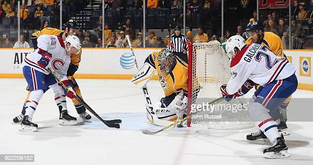 Pekka Rinne of the Nashville Predators blocks a wrap around shot by Alex Galchenyuk of the Montreal Canadiens as Daniel Carr battles against...