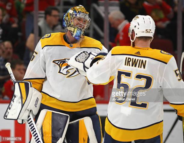 Pekka Rinne of the Nashville Predators celebrates a win against the Chicago Blackhawks and his first career goal an empty net shot with Matt Irwin at...