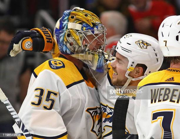 Pekka Rinne of the Nashville Predators celebrates a win against the Chicago Blackhawks and his first career goal an empty net shot with Viktor...
