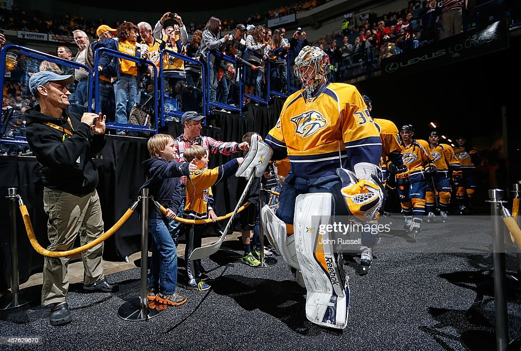 Pekka Rinne #35 of the Nashville Predators fist bumps fans as the team takes the ice against the Arizona Coyotes at Bridgestone Arena on October 21, 2014 in Nashville, Tennessee.