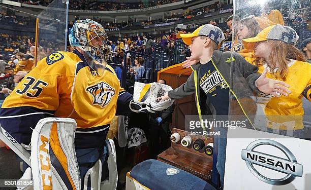Pekka Rinne of the Nashville Predators gives a puck to a young fan after warmups prior to an NHL game against the New York Rangers at Bridgestone...