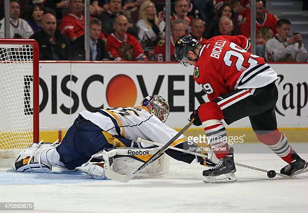 Pekka Rinne of the Nashville Predators knocks the puck away from Bryan Bickell of the Chicago Blackhawks in Game Four of the Western Conference...