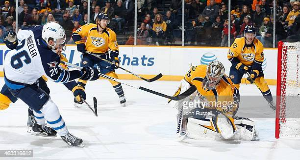 Pekka Rinne of the Nashville Predators makes a glove save against Blake Wheeler of the Winnipeg Jets during an NHL game at Bridgestone Arena on...