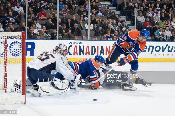 Pekka Rinne of the Nashville Predators makes a stop in close against Ryan Stone of the Edmonton Oilers at Rexall Place on January 12 2010 in Edmonton...