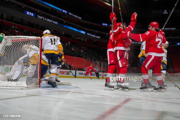 Pekka Rinne of the Nashville Predators pulls the puck out of the net as Dylan Larkin of the Detroit Red Wings and teammates congratulate Sam Gagner...