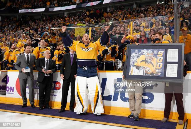 Pekka Rinne of the Nashville Predators raises the silver stick presented to him by GM David Poile for his 500th career NHL game prior to a game...