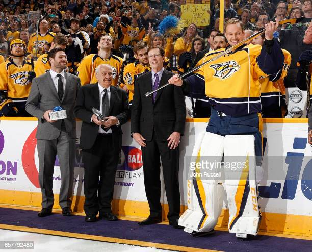Pekka Rinne of the Nashville Predators receives his silver stick from GM David Poile for his 500th career NHL game prior to a game against the San...