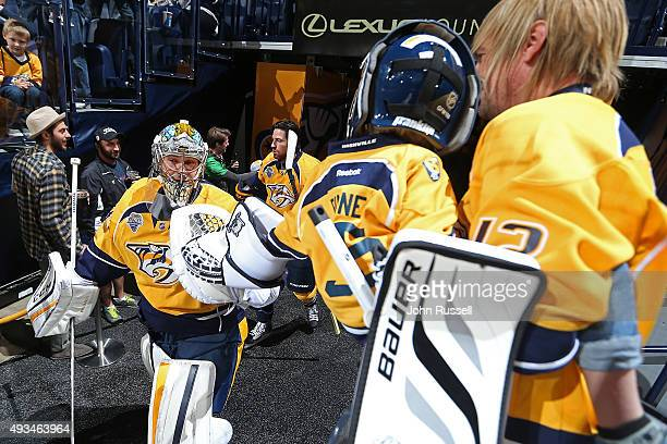 Pekka Rinne of the Nashville Predators taps gloves with a young fan as he takes the ice against the Tampa Bay Lightning during an NHL game at...