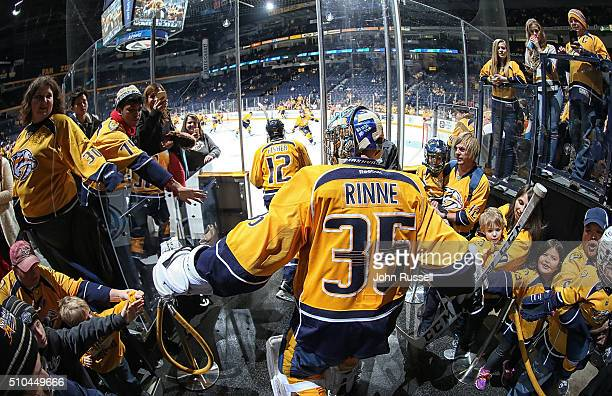 Pekka Rinne of the Nashville Predators taps hands with fans as he takes the ice prior to an NHL game against the Dallas Stars at Bridgestone Arena on...