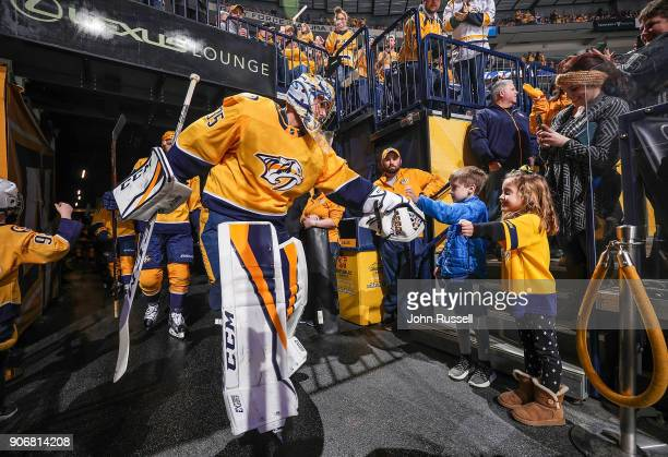 Pekka Rinne of the Nashville Predators taps hands with young fans as he takes the ice prior to an NHL game against the Arizona Coyotes at Bridgestone...