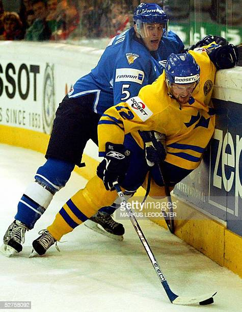 Pekka Saravo of Finland fights for the puck with Daniel Sedin of Sweden in the Group C match between Finland and Sweden the IIHF Men's World...