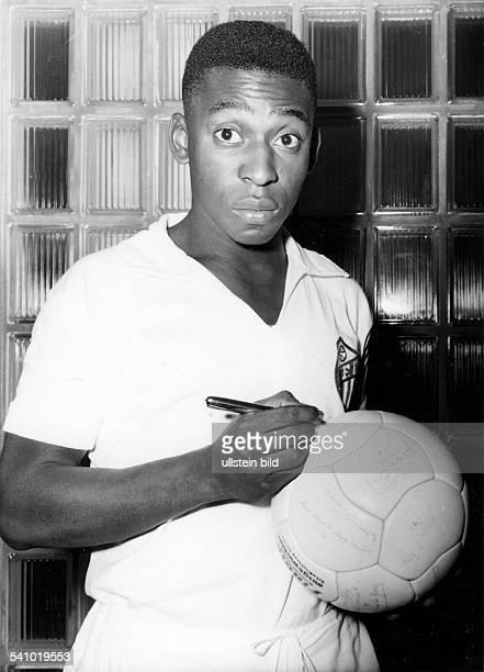 Pelé *Fussballspieler Brasilien Weltmeister 1958 1970'Sportler des Jahrhunderts' Halbportrait gibt Autogramme auf einen Fussball undatiert